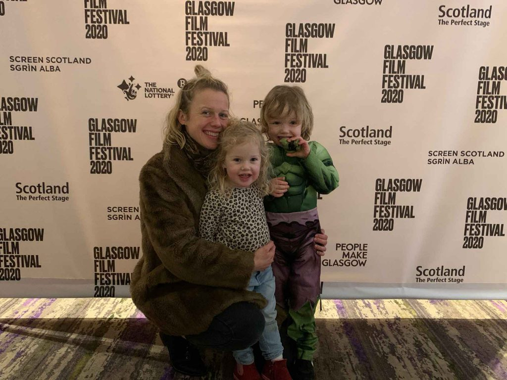 Image of a parent with their two children at a film festival